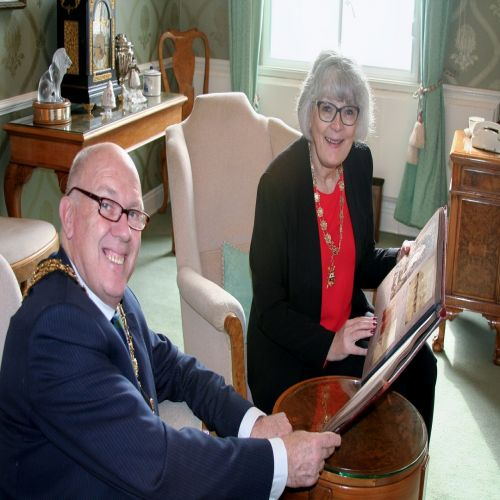 Mayor and Mayoress inspecting photo album of william Borough Hill