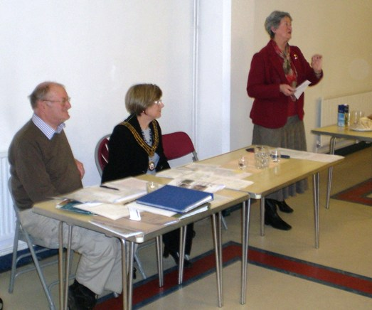 Jacky Barnes, editor of the Review, presenting her annual report to the members at the AGM, seated Arthur Jeffery acting chair and the president [2010] the mayor Liz Mizon. Image Will Temple